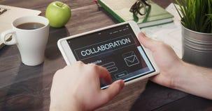 Verificando a informação da colaboração usando a tabuleta digital na mesa filme