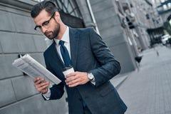 Verificando notícias de negócios O homem novo bonito no terno completo leu foto de stock royalty free