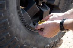 Verificando a pressão do pneumático Foto de Stock