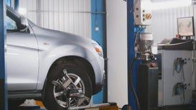 Verificando a roda no serviço do automóvel da garagem, fim acima Fotos de Stock