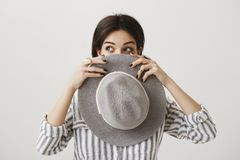 Verifichi il mio nuovo cappello d'avanguardia Ritratto di bella donna europea alla moda che guarda da parte con l'espressione cur Fotografia Stock