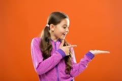Verifique isto para fora A cara feliz da criança mostra algo no espaço aberto da cópia da palma A menina demonstra o produto Prop fotografia de stock