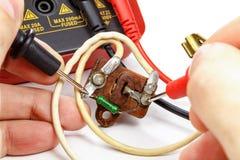 Verifique o resistor do vintage com o multímetro em um fundo branco imagens de stock