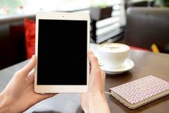 Verifique a tabuleta no café durante o trabalho Fotos de Stock