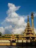 Veritical view of Wat and Pagoda with White Cloud, Burma (Myanma. Golden stupa structure shining in late afternoon sun in Burma (Myanmar), with overhanging eave Royalty Free Stock Photos
