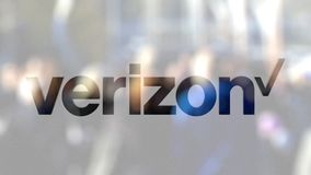 Verizon Communications logo on a glass against blurred crowd on the steet. Editorial 3D rendering
