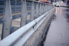 Verja cerca del camino mojado Fotografía de archivo