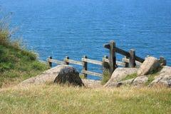 Verja de madera con la trayectoria abajo al océano azul Foto de archivo libre de regalías