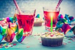 Verjaardag met cake, kaars, dranken en partijhulpmiddelen stock foto