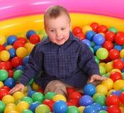 Verjaardag van pretjongen in ballen. Stock Afbeeldingen