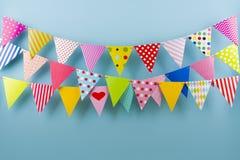 Verjaardags fest slingers van kleurrijke driehoekige vlaggen op blauwe achtergrond royalty-vrije stock fotografie