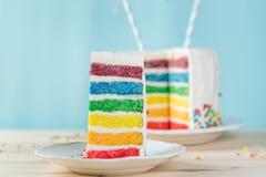 Verjaardagsachtergrond - gestreepte regenboogcake met het witte berijpen Stock Afbeeldingen
