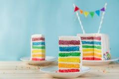 Verjaardagsachtergrond - gestreepte regenboogcake met het witte berijpen Royalty-vrije Stock Afbeelding