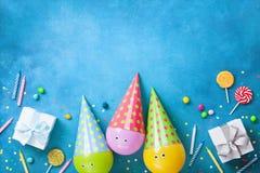 Verjaardagsachtergrond met grappige ballons in kappen, giften, confettien, suikergoed en kaarsen Vlak leg De kaart van de groet m royalty-vrije stock foto