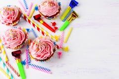 Verjaardagsachtergrond met roze cupcakes en kaarsen Royalty-vrije Stock Foto