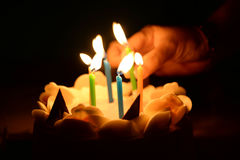 Verjaardagscake met hand brandende kaarsen in dark Stock Afbeeldingen