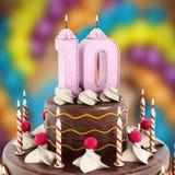 Verjaardagscake met nummer 10 aangestoken kaars Stock Afbeeldingen
