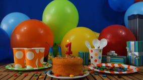 Verjaardagscake op rustieke houten lijst met achtergrond van kleurrijke ballons, giften, plastic koppen en plastic plaat met suik Stock Foto's
