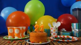 Verjaardagscake op rustieke houten lijst met achtergrond van kleurrijke ballons, giften, plastic koppen en plastic plaat met suik Stock Fotografie