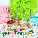 Verjaardagsconcept met cupcakes, naambord en decoratie voor een pretpartij op een witte achtergrond De groetkaart van de verjaard stock foto's