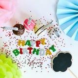 Verjaardagsconcept met cupcakes, naambord en decoratie voor een pretpartij op een witte achtergrond De groetkaart van de verjaard royalty-vrije stock foto