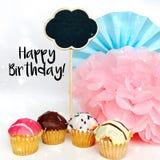 Verjaardagsconcept met cupcakes, naambord en decoratie voor een pretpartij op een witte achtergrond De groetkaart van de verjaard royalty-vrije stock foto's