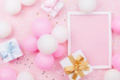 Verjaardagsmodel met kader, giftvakje, pastelkleurballons en confettien op de roze mening van de lijstbovenkant Vlak leg samenste stock foto's