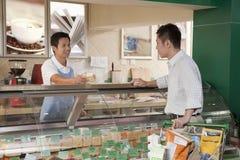 Verkäufe sind Mann entgegengesetzt unterstützen am Feinkostgeschäft, Peking als Angestellter tätig stockfotos