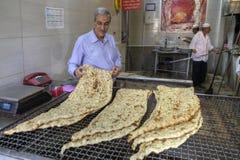 Verkäufer betrachtet frisch gebackenes iranisches lavash im traditiona Lizenzfreies Stockbild