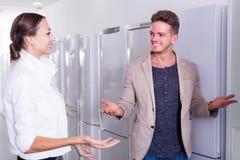 Verkäufer bietet einer Hilfe der jungen Frau an, Küchenkühlschrank zu kaufen Stockfoto