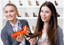 Verkäufer bietet Stöckelschuhe für den Kunden an Stockbild
