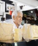 Verkäufer-At Counter In-Käse-Shop Stockfoto