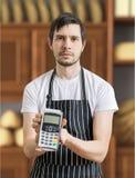 Verkäufer in der Bäckerei führt Zahlungsanschluß für das Zahlen mit Kreditkarte Lizenzfreies Stockbild