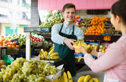 Verkäufer, der Bananen wiegt Stockbild