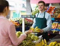 Verkäufer, der Bananen wiegt Stockfoto