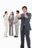 Verkäufer, der Daumen mit Kollegen hinter ihm aufgibt Lizenzfreie Stockbilder