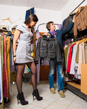 Verkäufer, der dem schönen Mädchen Lederjacke zeigt Stockbild