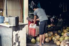 Verkäufer, der einen Eisblock für die Kokosnussgetränke schneidet, die er anbietet Stockfotografie