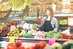 Verkäufer der erwachsenen Frau, der Obst und Gemüse wiegt lizenzfreie stockfotografie