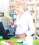 Verkäufer der erwachsenen Frau, der Zusammenstellung von Pflegemitteln überprüft lizenzfreie stockfotos