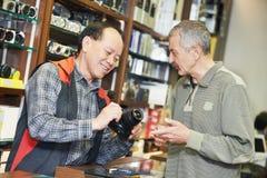 Verkäufer, der Fotokamera zum Käufer demonstriert Lizenzfreie Stockfotos