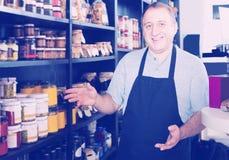 Verkäufer, der im Delikatessenabschnitt des gewöhnlichen Lebensmittelgeschäfts arbeitet stockfotografie