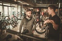 Verkäufer, der interessiertem Kunden ein neues Fahrrad im Fahrradshop zeigt Stockfotografie