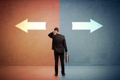 Verkäufer, der vor zwei Pfeilen auf blauem und rotem backgro steht Lizenzfreie Stockfotos