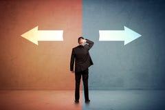 Verkäufer, der vor zwei Pfeilen auf blauem und rotem backgro steht Lizenzfreie Stockbilder