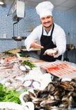 Verkäufer in der weißen Kappe und schwarzen im Schutzblech, die entgegengesetzt mit Fischen darstellt lizenzfreies stockfoto