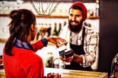 Verkäufer, der Zahlung mit Bankkarte Leser und Smartphone nimmt lizenzfreie stockfotografie