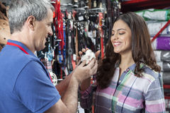 Verkäufer And Female Customer, das mit Meerschweinchen spielt lizenzfreie stockbilder