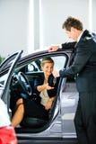 Verkäufer gibt dem Automädchen Schlüssel Stockfoto