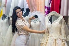 Verkäufer im Heiratssalon, der Kleider für Braut zeigt lizenzfreie stockbilder